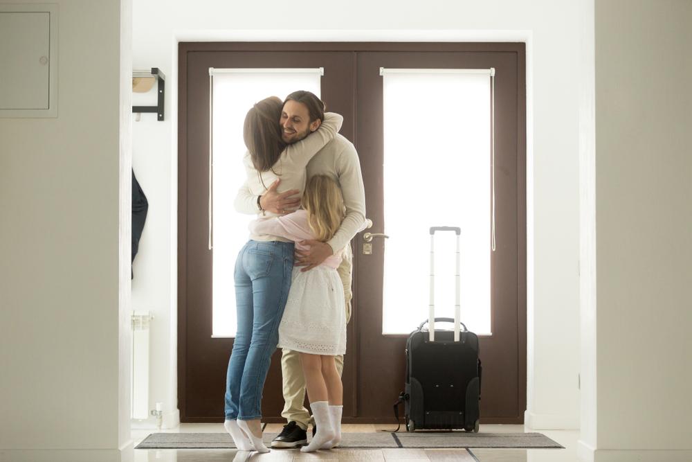 Vater wird an der Haustür von seiner Frau und seinem Kind in den Arm genommen