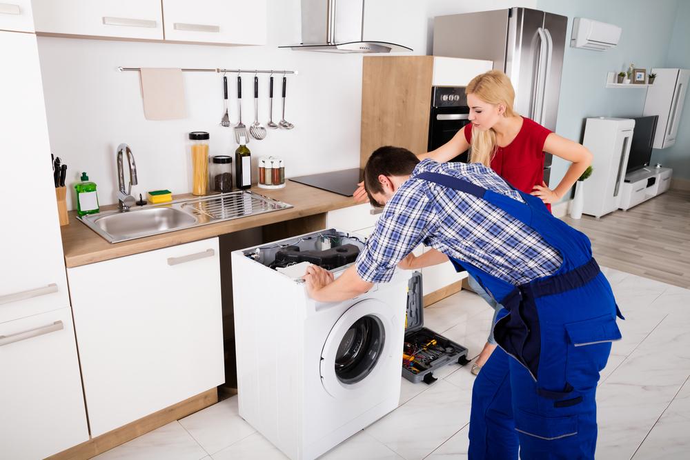 Frauen sehen junge männliche Arbeitnehmer mit Werkzeugkasten-Reparatur der Waschmaschine im Küchenraum