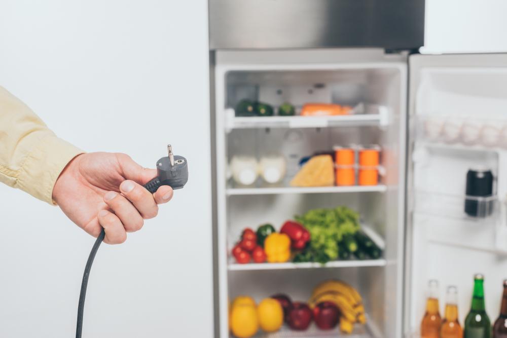 Ausschnitt eines Mannes, der das Stromkabel eines Kühlschranks hält