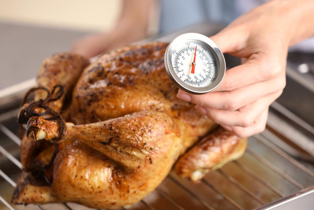Junge Frau, die die Temperatur von geröstetem Puten mit Fleischthermometer misst